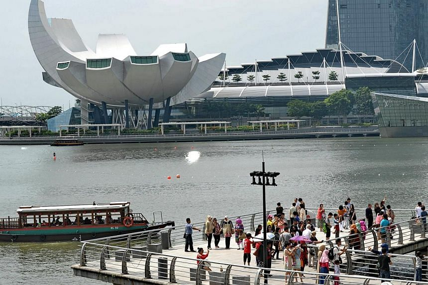 Tourists view the Marina Bay Sands resort hotel and casino from a pier at Merlion park in Singapore on June 24, 2014.The tourism receipt tally in Singapore rose to $6 billion in the first quarter of 2014, a five per cent increase on the same pe