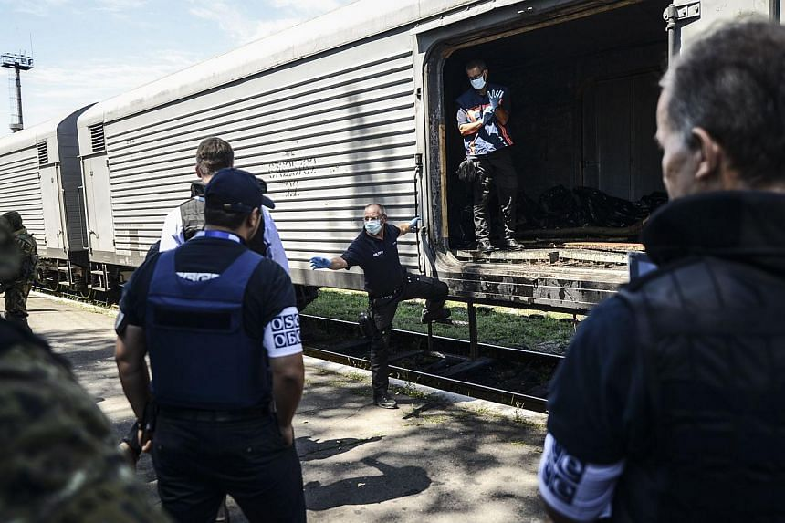 Monitors from the Organisation for Security and Cooperation in Europe (OSCE) and members of a forensic team inspect a refrigerator wagon containing the remains of victims from the downed Malaysia Airlines Flight MH17 at a railway station in the easte