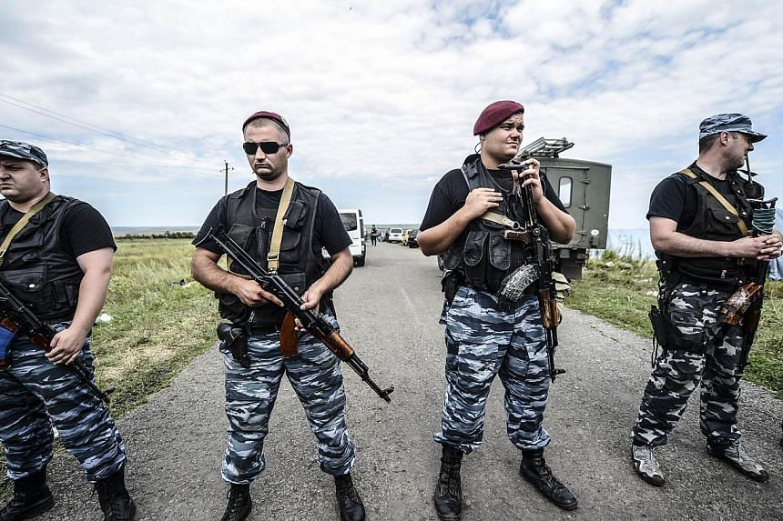 Armed pro-Russian separatists block the way to the crash site of Malaysia Airlines Flight MH17, near the village of Grabove, in the region of Donetsk on July 20, 2014. -- PHOTO: AFP