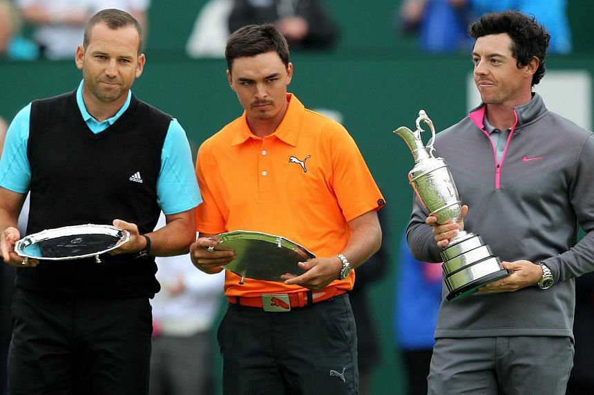 Spain's Sergio Garcia (left) and US golfer Rickie Fowler stand with their second place trophies beside Northern Ireland's Rory McIlroy (right) after finishing two strokes behind winner at Royal Liverpool Golf Course in Hoylake, north west England on