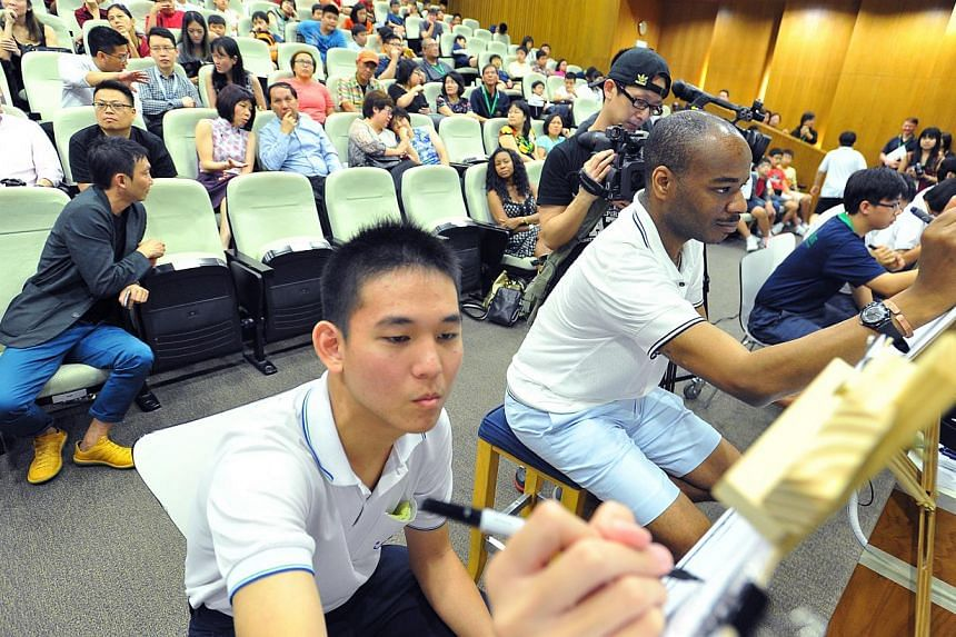 Mr Glenn Phua Yijue, (left) 17, student in Pathlight School's Vocational Track, sketching beside British artist Stephen Wiltshire at Pathlight School on July 21, 2014. -- ST PHOTO: LIM YAOHUI FOR THE STRAITS TIMES