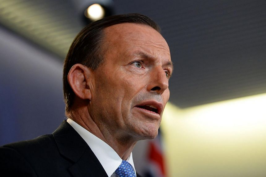 """Australian Prime Minister Tony Abbott demanded on Sunday that the bodies of those killed when Malaysia Airlines Flight MH17 crashed be """"treated with respect"""" and said he feared interference with evidence would continue. -- PHOTO: AFP"""