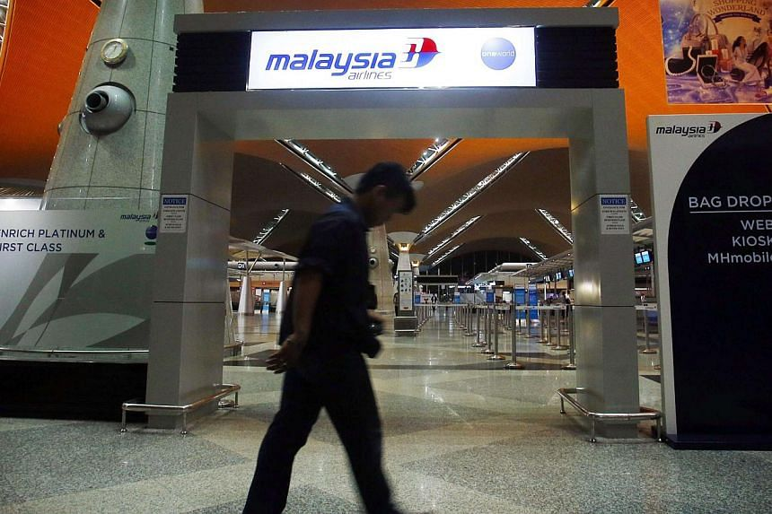 A man walks past the Malaysia Airlines check-in area at Kuala Lumpur International Airport in Sepang on July 18, 2014. -- PHOTO: REUTERS