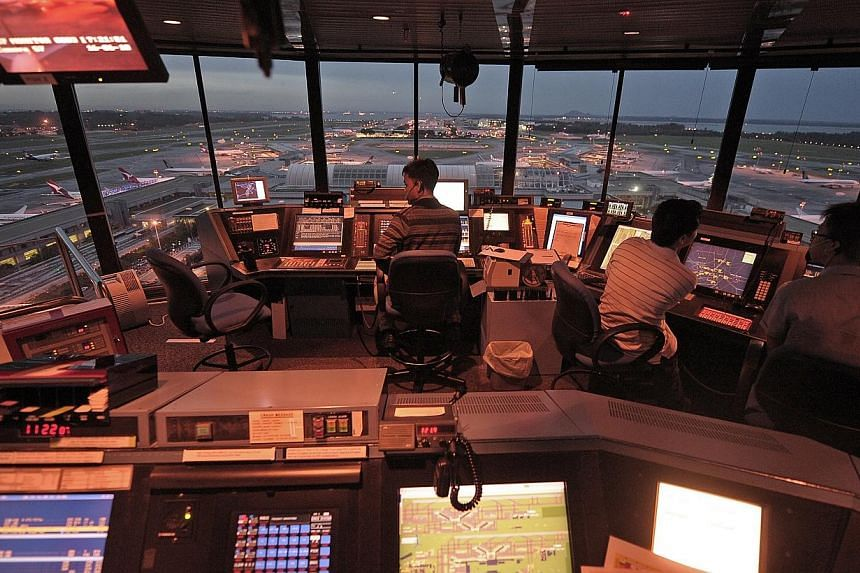 Air traffic controllers work inside the iconic Changi Airport control tower.Scholarships in the aviation industry are highly sought after by A-Level and International Baccalaureate (IB) Diploma graduates, a new survey has found. -- PHOTO: ST FI
