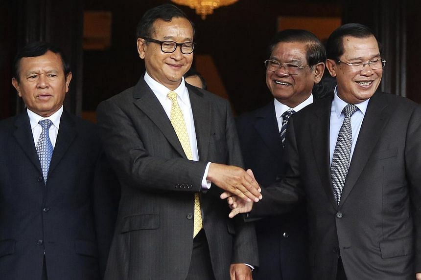 Cambodia's Prime Minister Hun Sen (second from right) shakes hands with Sam Rainsy (second from left), president of the Cambodia National Rescue Party (CNRP), after a meeting at the Senate in central Phnom Penh on July 22, 2014. -- PHOTO: REUTER