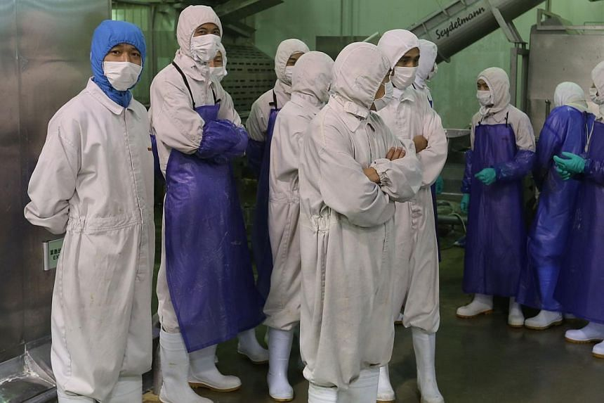 Workers standing aside as inspectors investigate the Shanghai Husi Food Co, a factory of US food provider OSI Group, in Shanghai on July 20, 2014. Chinese police are questioning staff of US food supplier OSI Group for selling expired meat, state