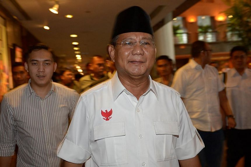 Indonesian candidate Prabowo Subianto (centre) walks with his team after a meeting in Jakarta on July 20, 2014.-- PHOTO: AFP