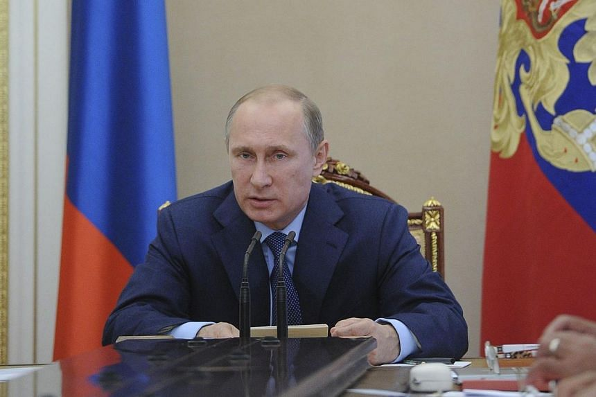 Russian President Vladimir Putin heads a meeting of the Security Council in Moscow's Kremlin on July 22, 2014. Russian President Vladimir Putin promised Tuesday, July 22, 2014, to do everything possible to influence pro-Russian separatists in eastern