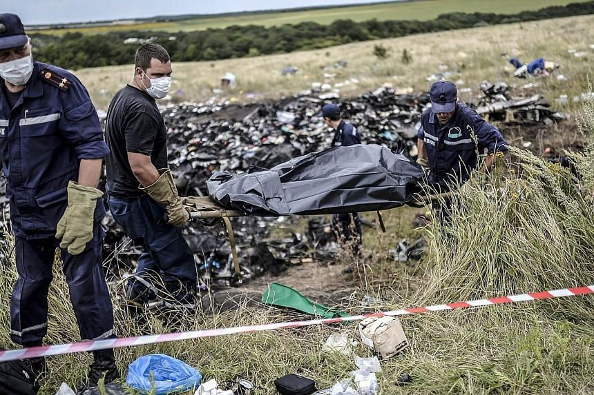 Ukrainian State Emergency Service employees collect bodies of victims at the site of the crash of a Malaysia Airlines plane in Grabove, in rebel-held east Ukraine on July 20, 2014. Malaysia's leaders worked quietly behind the scenes to secure th