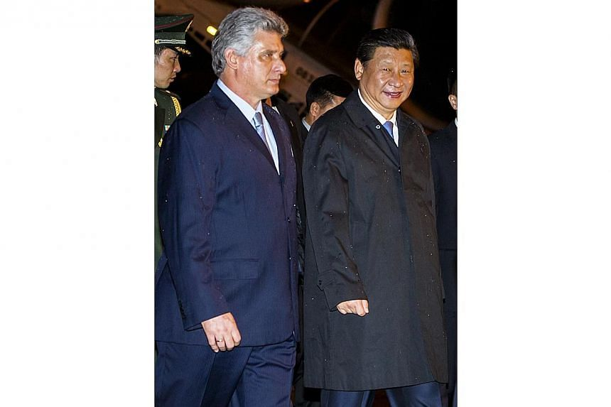 China President Xi Jinping (right) is welcomed by Cuban Vice-President Miguel Diaz Canel (left) at Havana International Airport Jose Marti on July 21, 2014. Chinese President Mr Xi Jinping visited Cuba on Tuesday, July 22, 2014, to expand invest