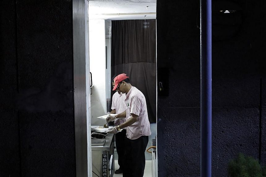 Inmates prepare to serve food inside the kitchen of a restaurant run by the Tihar Jail authorities on Jail Road in west Delhi on July 21, 2014. -- PHOTO: REUTERS