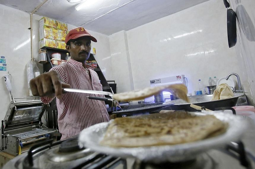 An inmate prepares food inside the kitchen of a restaurant run by the Tihar Jail authorities on Jail Road in west Delhi on July 21, 2014. -- PHOTO: REUTERS