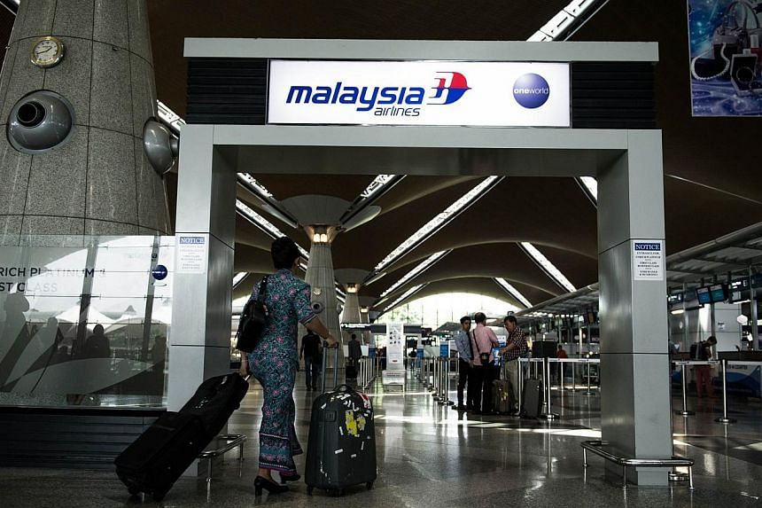 A Malaysia Airlines flight attendent walks at Kuala Lumpur International Airport in Sepang on July 21, 2014. -- PHOTO: AFP