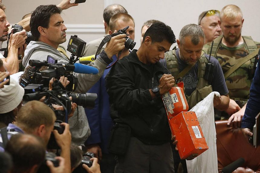 A Malaysian expert (centre) examines a black box belonging to Malaysia Airlines flight MH17 during its handover from pro-Russian separatists, in Donetsk on July 22, 2014. -- PHOTO: REUTERS