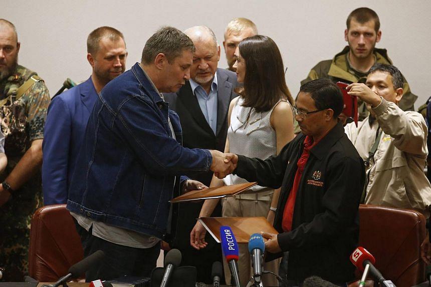 A representative (front, left) from pro-Russian separatists shakes hands with Colonel Mohamed Sakri (front right) of the Malaysian National Security Council after signing documents on the handing over of Malaysia Airlines flight MH17's black boxes, i