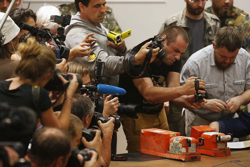 Members of the media take pictures of black boxes belonging to Malaysia Airlines flight MH17, before their handover from Ukrainian pro-Russian separatists to Malaysian representatives, in Donetsk on July 22, 2014. -- PHOTO: AFP