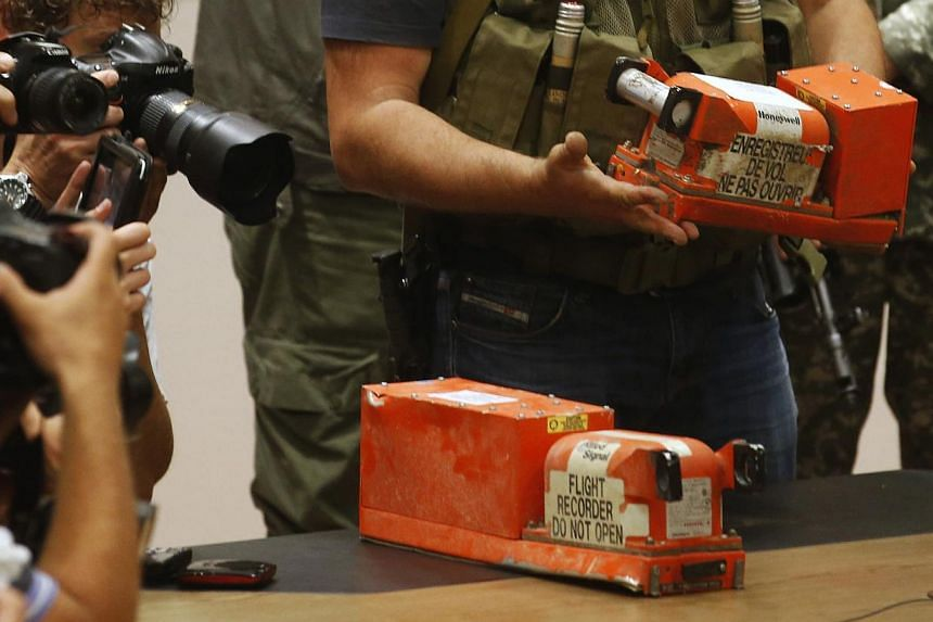 Members of the media take pictures as a pro-Russian separatist places black boxes belonging to Malaysia Airlines flight MH17 on a desk, before their handover to Malaysian representatives, in Donetsk on July 22, 2014. -- PHOTO: REUTERS