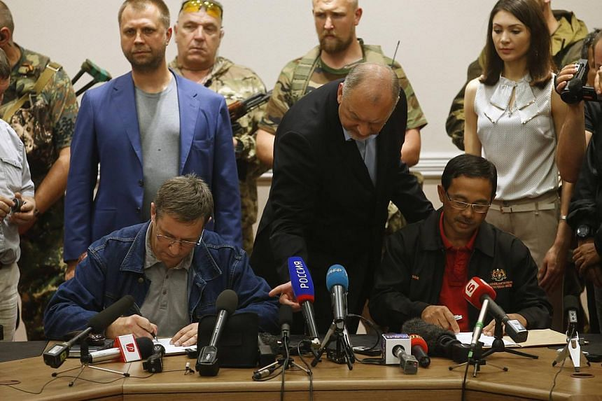 A representative (seated, left) from pro-Russian separatists and Colonel Mohamed Sakri (seated, right) of the Malaysian National Security Council sign documents after the handing over of Malaysia Airlines flight MH17's black boxes, in Donetsk on July