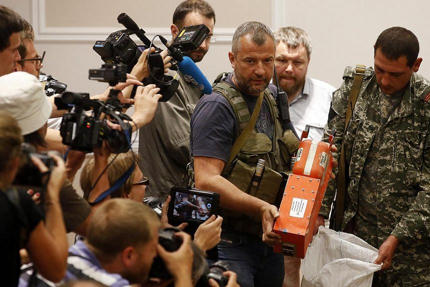 A pro-Russian separatist shows members of the media a black box belonging to Malaysia Airlines flight MH17, before its handover to Malaysian representatives, in Donetsk on July 22, 2014. -- PHOTO: REUTERS