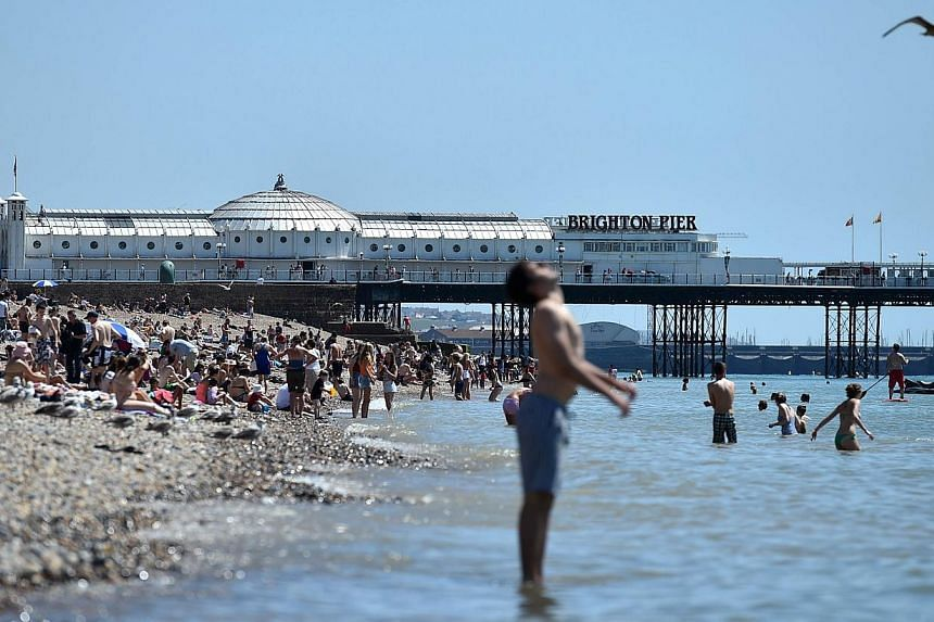 People enjoy the hot weather on Brighton beach in Sussex, southern England, on July 17, 2014. -- PHOTO: AFP