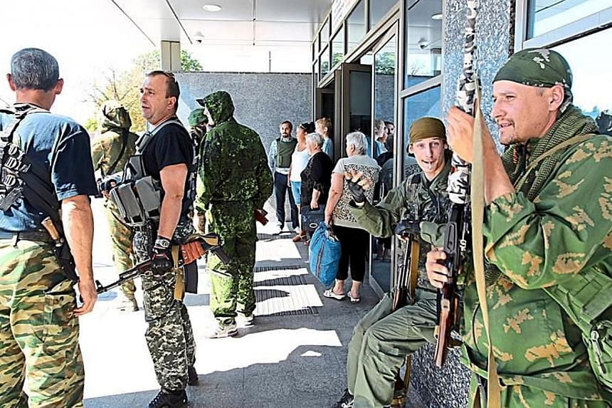 DPR soldiers standing guard as railway passengers wait at an underground tunnel in the Donetsk train station for the gunfire outside to subside. -- PHOTO:  THE STAR/ASIA NEWS NETWORK