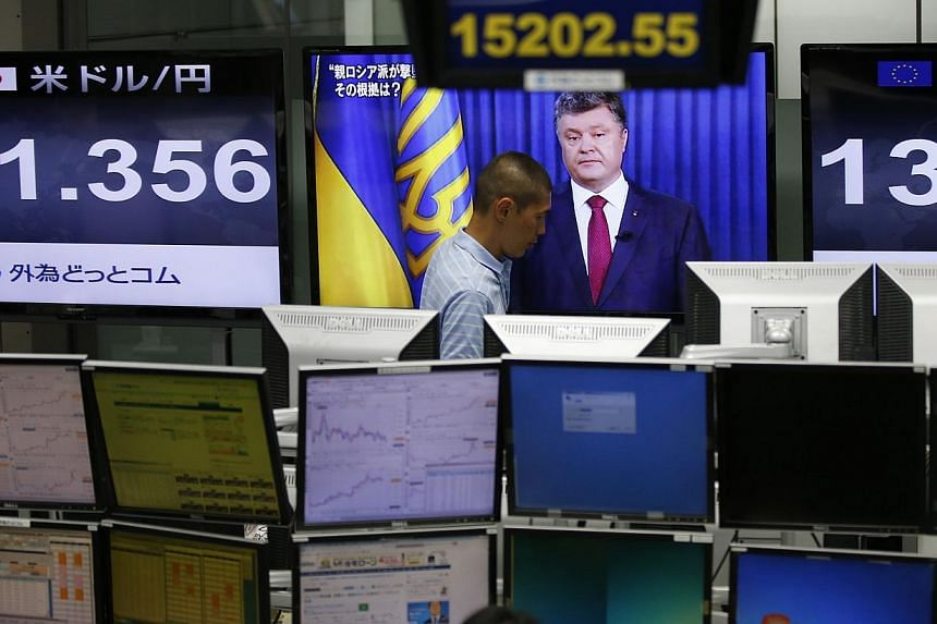 An employee of a foreign exchange trading company in Tokyo walks past a monitor showing Ukrainian President Petro Poroshenko. Asian markets picked up on Tuesday with traders welcoming news that pro-Russian rebels had handed over the black boxes from
