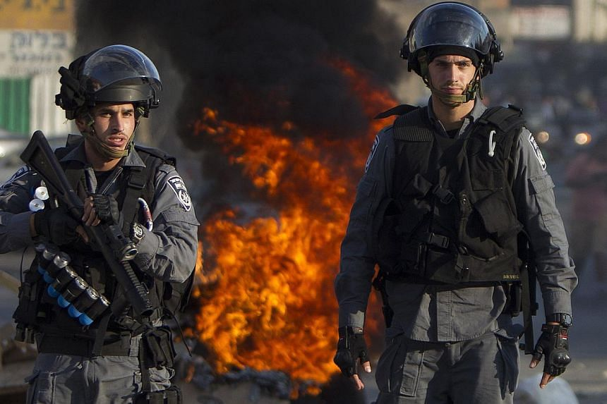 Israeli riot police keep watch during clashes that followed a protest against Israel's military offensive on the Gaza Strip, in the northern city of Nazareth, on July 21, 2014. -- PHOTO: AFP