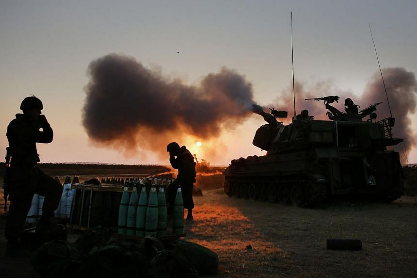 Israeli soldiers of the 155mm artillery cannons unit fire towards the Gaza Strip from their position near Israel's border with the coastal Palestinian enclave, on July 21, 2014. -- PHOTO: AFP