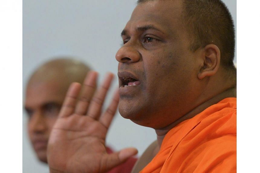 In this photograph taken on March 29, 2013 , Sri Lankan Buddhist monk Galagodaatte Gnanasara speaks during a press conference in Colombo, denying involvement in an overnight attack against a Muslim-owned clothing store just outside the capital. The i