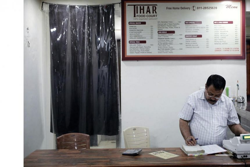 Kishan Singh Bisht, a jail warden in Tihar, maintains a register inside a restaurant run by the Tihar Jail authorities on Jail Road in west Delhi on July 21, 2014. -- PHOTO: REUTERS