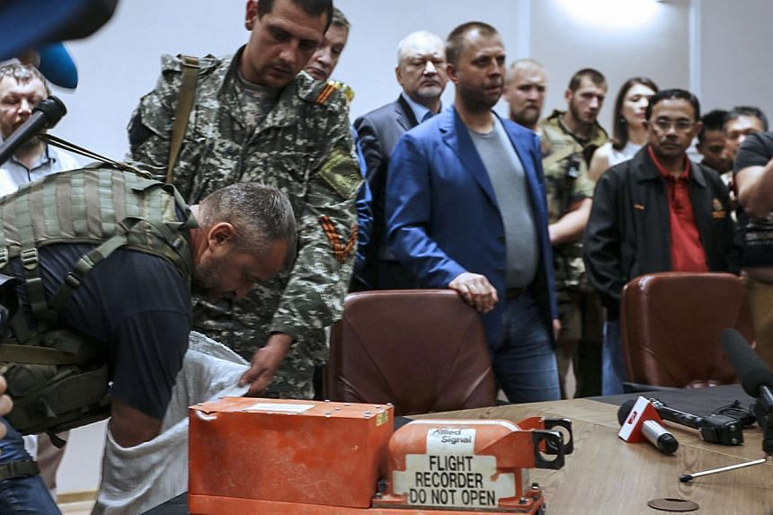 A pro-Russia separatist shows members of the media a black box belonging to Malaysia Airlines flight MH17, before handing it over to Malaysian representatives during a press conference in Donetsk on July 22, 2014.Malaysia said on Tuesday it wil