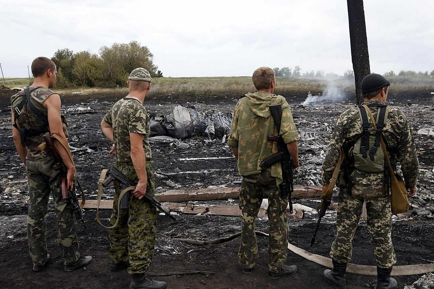 Armed pro-Russian separatists stand at the site of a Malaysia Airlines Boeing 777 plane crash near the settlement of Grabovo in the Donetsk region,on July 17, 2014.The downing of the MH17 flight over rebel territory in Ukraine has put Moscow's