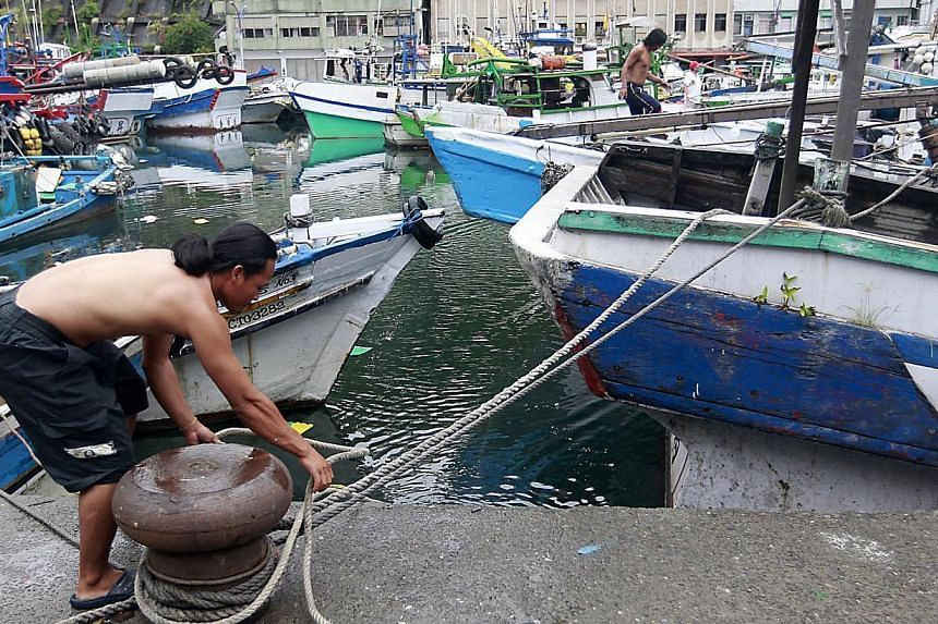 A fisherman ties his boat up as Typhoon Matmo approaches the north-eastern coastal town of Nanfangao in Ilan county, northern Taiwan, on July 22, 2014. The Taiwan military was collecting and distributing sandbags to guard against possible floodi