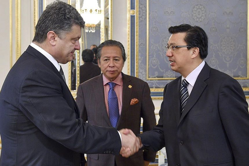Ukrainian President Petro Poroshenko (left) welcoming Malaysian Foreign Minister Anifah Aman (centre) and Malaysia's transport minister Liow Tiong Lai (right) during their meeting in Kiev on July 21, 2014, prior to talks. -- PHOTO: AFP