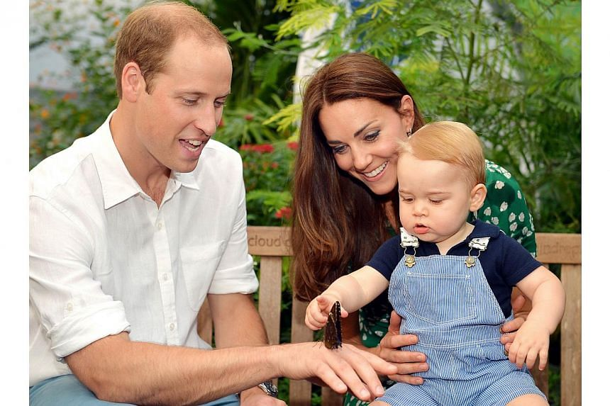 A photograph taken in London on Wednesday July 2, 2014, to mark Britain's Prince George's first birthday, shows Prince William (left) and Catherine, Duchess of Cambridge with Prince George during a visit to the Sensational Butterflies exhibition at t