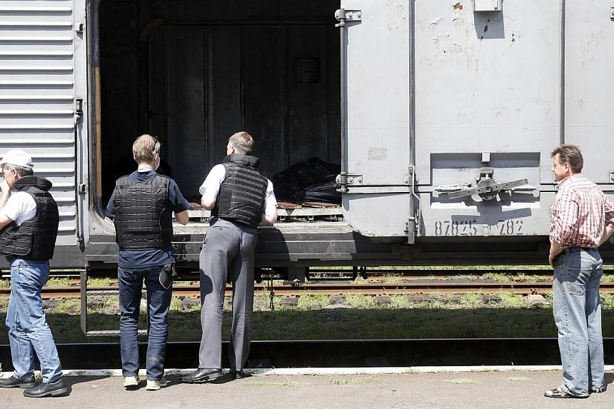 Monitors (left) from the Organization for Security and Cooperation in Europe inspect a refrigerator wagon, which according to employees and local residents contains bodies of passengers of the crashed Malaysia Airlines Boeing 777 plane, at a railway