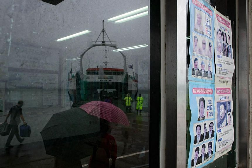 In a photo taken on July 6, 2014 a wanted poster for fugitive Chonghaejin owner Yoo Byung-Eun is displayed in a window in Jindo harbour, where families of the victims of the Sewol ferry still unaccounted for continue to wait. -- PHOTO: AFP