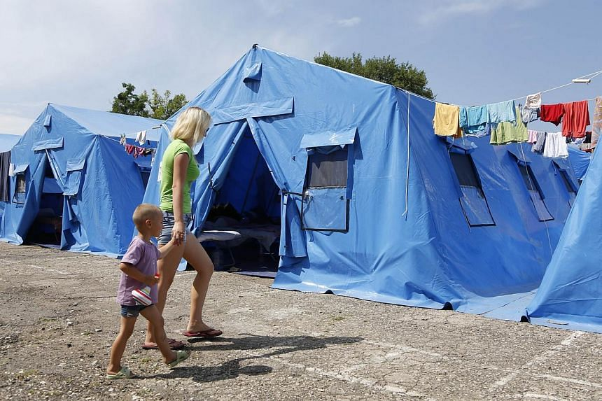A woman with a child walk at a temporary facility for refugees form Eastern Ukraine, 20 km outside from the Crimean capital Simferopol, on July 17, 2014. Kiev and the West blame Moscow for fuelling the fighting but those leaving the rebels' self-proc
