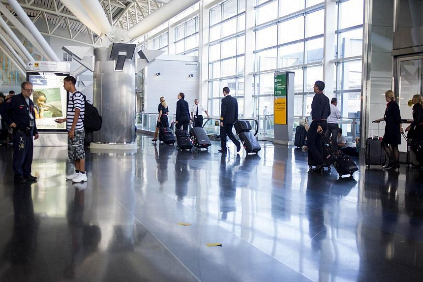 People walk in the American Airlines/US Airways Terminal at John F. Kennedy Airport in New York City on July 22, 2014. The Federal Aviation Administration (FAA) has halted all flights from the US to Tel Aviv, Israel following a rocket attack near Ben