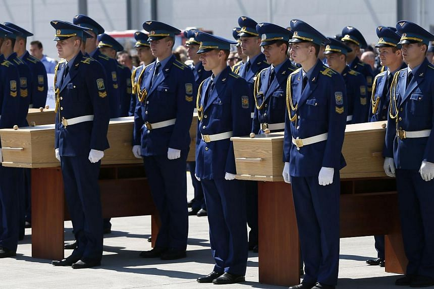 Honour guards take part in a ceremony with coffins of some of the victims of Malaysia Airlines MH17, which was downed over rebel-held territory in eastern Ukraine, before they are loaded onto a transport plane heading to the Netherlands at Kharkiv ai