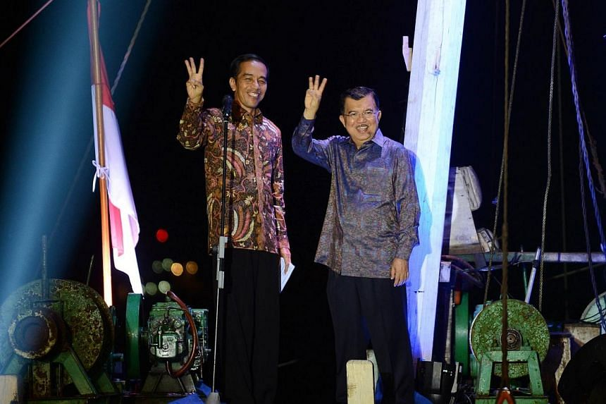 Indonesian presidential candidate Joko Widodo (left) waves with his running mate Jusuf Kalla (right) after delivering his victory address aboard a traditional commercial boat in Jakarta's port district of Sunda Kelapa on July 22, 2014 as the Ge