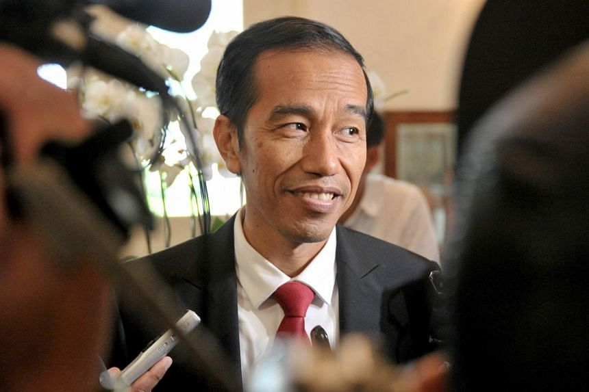 Indonesian president elect Joko Widodo (centre) answers questions from the media in Jakarta on July 23, 2014 as he returns to work after the General Elections Commission declared him the winner of the presidential elections.-- PHOTO: AFP