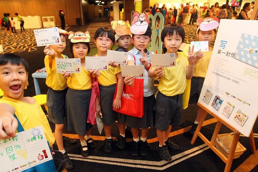 Pupils flashing postcards of their thoughts and wishes for their families at a Lianhe Zaobao exhibition booth on Sep 14, 2013.Registration is open for sharing sessions and workshops at the Mother Tongue Languages (MTL) Symposium to be held on A