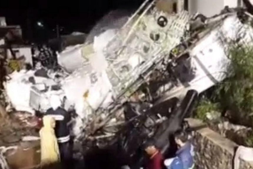 A TransAsia Airways plane carrying 58 people from south-western Taiwan's Kaohsiung city has crashed into two houses on Wednesday, killing dozens of people. -- PHOTO: APPLE DAILY