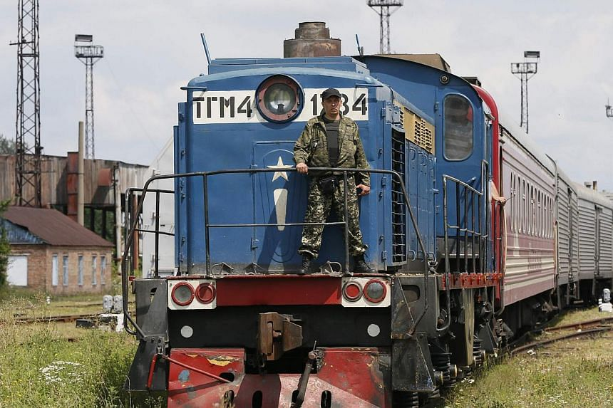 A guard stands on a train carrying the remains of victims of Malaysia Airlines MH17 downed over rebel-held territory in eastern Ukraine after it arrived in the city of Kharkiv, eastern Ukraine on July 22, 2014. -- PHOTO: REUTERS