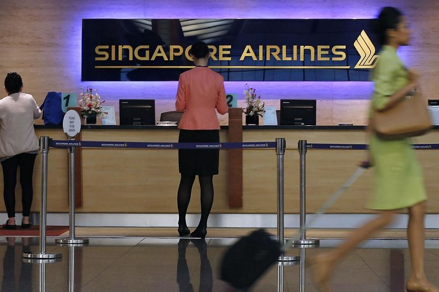 People walk past a Singapore Airlines ticketing counter at Changi Airport in Singapore. SIA, which has been criticised for flying over Ukraine before Thursday's Malaysia Airlines crash, has confirmed that it had been avoiding parts of the country's a