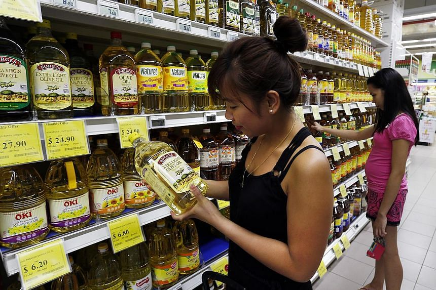 Consumers looking at the healthier cooking oils on display at a Sheng Siong supermarket. Sales of canola oil, soya bean oil and sunflower oil at the supermarket chain rose by 60 per cent last year, compared with that in 2011.