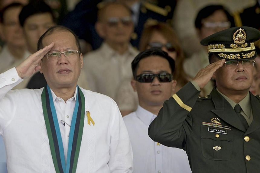Philippine President Benigno Aquino salutes during a change of command ceremony with incoming Armed Forces of the Philippines Chief of Staff General Gregorio Pio Catapang (right) at military headquarters in Manila on July 18, -- PHOTO: AFP