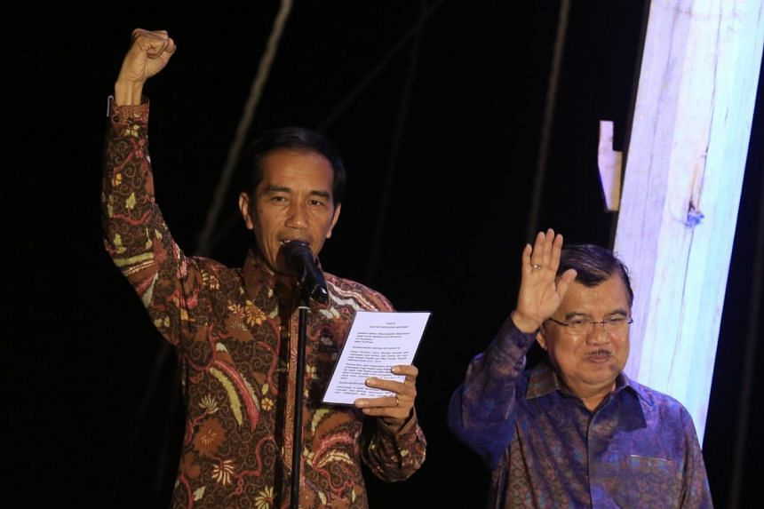 Indonesian presidential candidate Joko Widodo (L) waves with his running mate Jusuf Kalla (R) after delivering his victory address aboard a traditional commercial boat in Jakarta's port district of Sunda Kelapa on July 22, 2014 as the General E