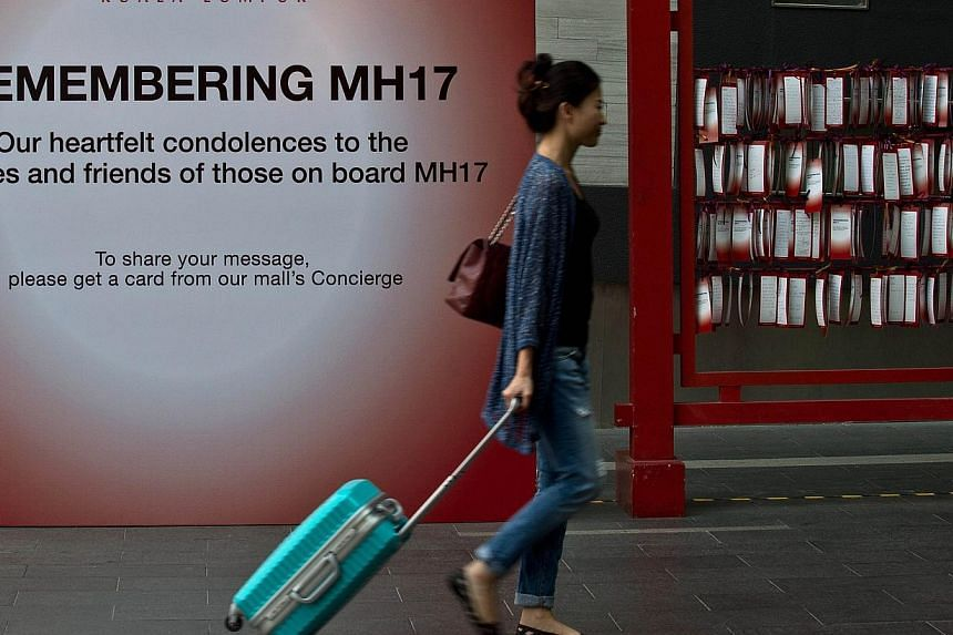 A tourist walks past a board with prayers and condolence messages for victims of the Malaysia Airlines MH17 flight, displayed on a board outside a shopping mall in Kuala Lumpur on July 23, 2014. -- PHOTO: AFP